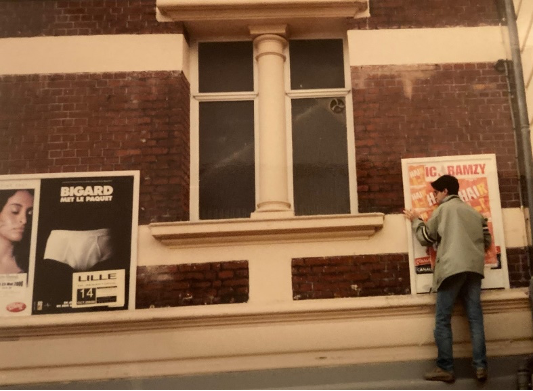 A person standing in front of a building with a sign  Description automatically generated with low confidence